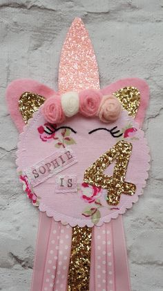 UNICORN PARTY BIRTHDAY ROSETTE BADGE Handmade Unicorn birthday rosette personalised with name and age. The top has unicorn ears, horns and cute mini felt roses. The bottom is trimmed with pretty ribbons to match the felt roses in pink and ivory. The age is appliqued on in gold glitter