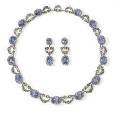 A Rare Sapphire & Diamond Necklace by Carl Fabergé formed from thirteen graduating clusters of oval, brilliant cut, blue sapphires encircled by rose cut diamonds, joined by rose & brilliant diamond set bows suspending diamond set floral swags supported on openwork galleries, set in silver & mounted on gold (later matching earrings). By Fabergé's Chief Jeweller: Albert Holmström. St Petersburg, 1908. http://www.wartski.com/ archive, Highlights 2011