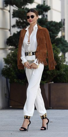 Miranda Kerr drapes a fringe jacket on top of her belted white jumpsuit with black/gold accents. // #Celebrity #StreetStyle