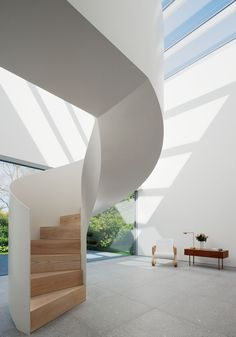 A spiral staircase provides an eye-catching feature inside this minimal white house »