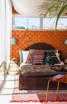 Bed against a brightly colored wallpaper wall.