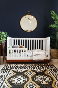 a modern copper planter, white modern toddler crib, a gold hoop mirror and a boho style rug create a masculine, cozy space for little Levi