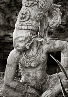 Travel photography in Mexico -- Statue of an ancient Mayan warrior in a jungle setting in Mexico's Riviera Maya region.