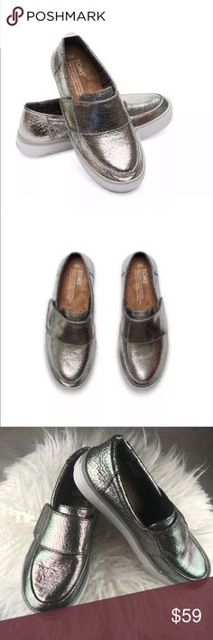 Toms Altair leather metallic slip on women shoes Product Description: The TOMS Altair plimsolls are the perfect slip-on shoe, appearing in cracked metallic uppers and featuring a velcro top-strap, the aztec lining and thick rubber outsole completes this design.  More information below.  Product Attributes:   Colour: Gunmetal  Main Upper Material: Leather  Main Outsole Material: Rubber  Lace-type: Slip On,Velcro  Gender: Womens  Minimal signs of wear from trying on otherwise new please see…