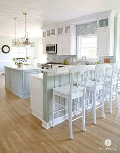 I'm in love with this gorgeous kitchen. Love the upper cabinets, the backsplash carried to the ceiling, the color of the island, and those light fixtures!