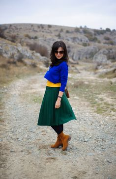 Colourful in the mountains:  green pleated skirt, cobalt blue top, brown boots, mustard top, crop top