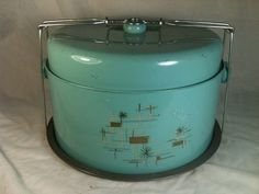 Vintage cake carrier...I practically have this exact one...same color only mine has a chef cooking something on the stove :D