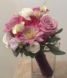 Bridesmaid bouquet in purples and lavenders.  Lavender Dahlias, purple roses, lavender lisianthus, white calla lilies, deep rose hydrangea, and white ranunculus.