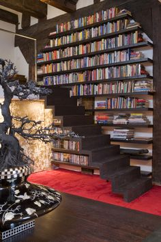 Loft by jeroen de Nijs (dark living room with lots of books and dark stairs)