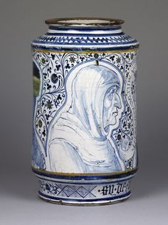 """Albarello with almost vertical sides. Earthenware apparently tin-glazed inside and out (not the foot). Painted one side with a man in a hood facing a nun; between them a scroll """"HUMILITAS ALTA PETIT"""". On the other side is a younger woman, her head covered, facing a man in a peaked hat. All figures within contour panels; floral tendrils between. Around the foot diamond panels and foliage; in Gothic letters """"sy. de. fumoterre"""" beneath the older pair."""