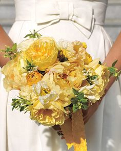 This sunny bouquet includes golden peonies, garden roses, honeysuckle, ranunculus, and poppies.