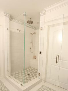 White marble field tiles are accented with a beautiful geometric mosaic featuring subtle green tones. The frameless glass enclosure creates an open feel and allows the tile work detail to spill out throughout the bathroom. The shower features a bench, a rain showerhead and a handheld showerhead in addition to the standard showerhead.