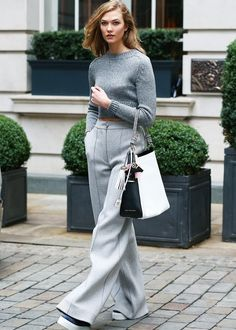 Karlie Kloss in London wearing a grey cropped sweater, grey wide-leg trousers, flatforms and hobo bag.