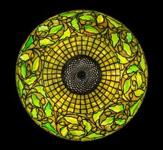 A Tiffany Studios Favrile Glass and Bronze Swirling Oak Lamp, circa 1910, the domed geometric shade decorated with a band of leaves and acorns, raised on a faceted stick base, the shade impressed Tiffany Studios New York 1467, the base impressed Tiffany Studios New York 533.