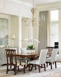 Armchairs and upholstered side chairs create a surprisingly casual combination around a classic table. - Traditional Home ®/ Photo: Emily Jenkins Followill / Design: Phoebe Howard
