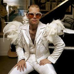 English pop singer Elton John in a flamboyant stage outfit of white suit with feather trim and rhinestone encrusted glasses, circa Get premium, high resolution news photos at Getty Images Gianni Versace, Pop Punk, Fred Mercury, Elton John Costume, Elton John Halloween Costume, Mode Disco, Fashion Art, 70s Fashion, Mundo Musical