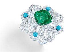 Ring in18K white gold set with1 cushion-cut emerald (approx. 7.29 cts), 12 marquise-cut diamonds (approx. 1.20 cts), 4 turquoise beads (approx. 0.50 ct) and 130 brilliant-cut diamonds (approx. 3.12 cts). Ref.: G34HH300 - Four–leaved flower–ring witha Colombian emerald <b>G34HH300 </b>