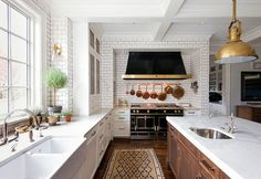 A subway tiled cooking nook is filled with a black kitchen hood with brass trim placed over a brass pot rack mounted on the backsplash as well as a black French stove, La Cornue Grand Palais 180.