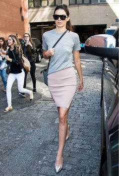 Kendall Jenner wears a gray tee with a pale pink skirt and metallic heels.