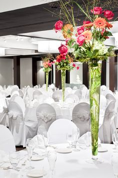 A really unique and pretty look in The Grand Ballroom at Weber's—white tables and chairs contrasted with vibrant flower arrangements. Gorgeous and cool.