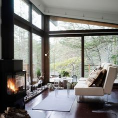Floor-to-ceiling windows and a fireplace. I would love to curl up here with coffee and a good book.