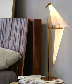 The Moooi Perch Lamp series features a balancing sculptural light made of folded paper and brass. The lamp takes the form of an abstract bird which appears to be delicately balanced on its metal perch.