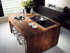 Rough hewn kitchen island with sleek ceramic cook top. A commodity of space and a strong visual centerpiece for a small kitchen.
