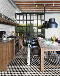 This is quite a funky kitchen . . . neutral scheme works so well with view of plants, industrial accessories, wood and graphic detailing on flooring . . .