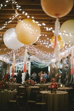 Love this whimsical wedding reception decor look with giant balloons and twinkly lights!
