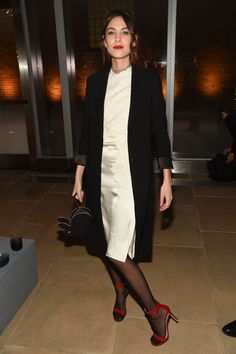 Alexa Chung accessorizes a simple white silk dress with a red lip and matching shoes.