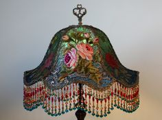 Lovely Art Nouveau 1920s lamp base holds an emerald green and teal silk Gish…