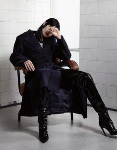 Manteau et corset en drap de laine, PRADA. Cuissardes, BALENCIAGA.