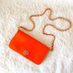 """Tory Burch Clutch Shoulder Bag *Authentic* Vibrant sunny orange (Tory's fav color ) patent leather clutch bag with removable shoulder strap. Stains/marks on back exterior of clutch from bleeding of color from another bag. Have not tried to remove so potential to be fixed. Some wear (scratches) on front gold closure piece. Interior in like new condition. Length of shoulder strap: 41"""". Used only a few times. Original dust bag included. Tory Burch Bags Shoulder Bags"""