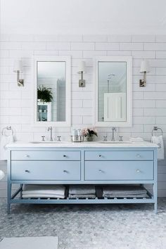Stunning bathroom features a sky blue double washstand topped with white marble fitted with his and her oval sinks and hook and spout faucets under white beveled mirrors illuminated by polished nickel sconces alongside a carrera marble hex tiled floor.