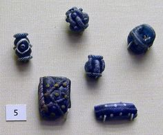Glass bead; cubical; pierced transversely in each direction; white hatched ornament on edges on blue ground.