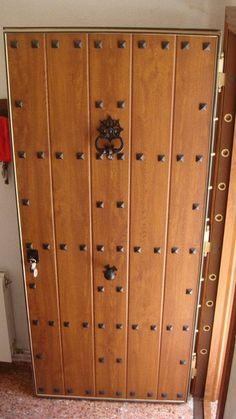 Puerta acorazada de seguridad estilo rústico con paneles de madera y tachuelas. Perfecta para casas de campo, casas rurales o decoraciones estilo rústico.