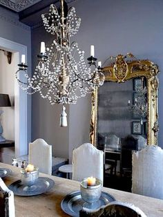 love the chandelier mirror and old chairs