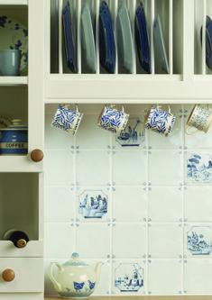Een landelijke/boeren keuken met blauwe afbeeldingen op de tegels.