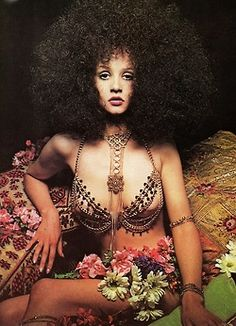 A 1969 Harpers Bazaar pictorial featuring a model in a dramatic Afro wig and body jewelry by Adrien Mann.