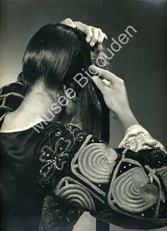 Pose de coiffe 1963 Deuxième étape : les cheveux sont remontés sur le bonnet à l'arrière de la tête. Ils sont lissés à l'aide d'un peigne puis maintenus par un ruban de velours noir et des épingles sur le sommet du crâne.