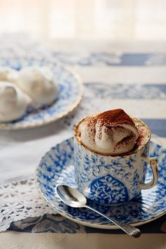 Coffee with whipped cream and cinnamon in a beautiful blue and white cup.