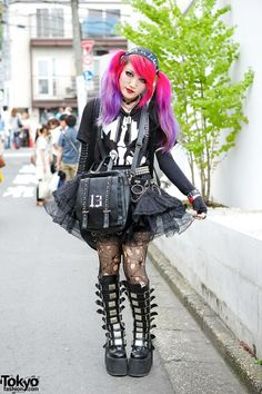 Montionless in White Tee, sheer skirt, funky bag, Knee length buckle boots, ripped tights, lilac bracelet, and accessories