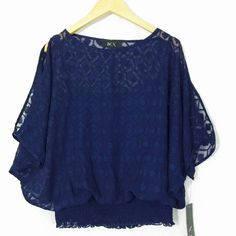NWT - BCX Solid Navy Blue lace Blouse Size XS BCX Solid Navy Blue lace Blouse Size XS Juniors    NWT - Retail $39.00 UPC Code: 637348077205 Style # 1056772  Product Features Slit Peek a boo shoulder Color Navy Blue  Elastic Waist  Fitting & Sizing Bust 27-in Waist 28-in Shoulder 20-in Length 22-in Sweep 28-in  Fabric & Care Imported (Vietnam) Polyester  Machine was / Line dry BCX Tops Blouses