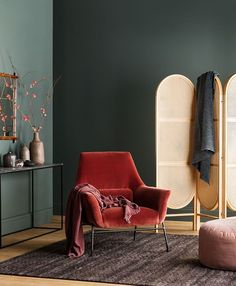 dark green wall sitting room with a velvet coral red color chair,
