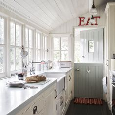 Lots of light in a country galley style kitchen. Love the red EAT letters above stable door.