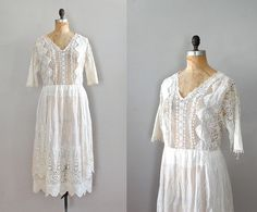 late Edwardian/early 1920s white bobbin lace, tatted lace and embroidered batiste tea dress with V collar, 3/4 sleeves and layered skirt. closes with hook and eye closures up the back. this dress is semi-sheer & a slip or underdress should be worn.