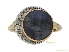 Labradorite 'man in the moon' ring. Set centrally with a round carved natural unenhanced labradorite in a closed back rubover setting, enhanced by fourteen graduating round rose cut diamonds in closed back grain and cutdown settings with a combined approximate weight of 0.14 carats, to a crescent shaped moon encircling the finely carved face of the 'man in the moon', flanked by trumpeting scrolling tri-split shoulders which taper through to a ridged D-shape shank. Tested ...