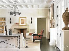 Plaster walls and a tray ceiling in the living room create a warm envelope for a dash of orange. The Barley twist chair, covered in fabric by Joseph Noble, and the iron sofa table are by Formations at Jerry Pair; the chandelier is by Dessin Fournir; and the mantel artwork is from Tew Galleries. Anything but Ordinary | Atlanta Homes & Lifestyles
