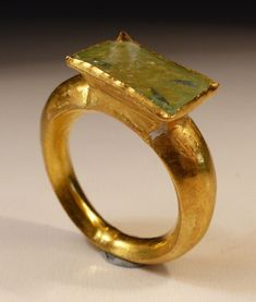 Hollow Gold Ring, having a thick graduated band supporting a square bezel set with glass sealing a beautiful fine gold cross, dating Circa 7th/8th Century AD.