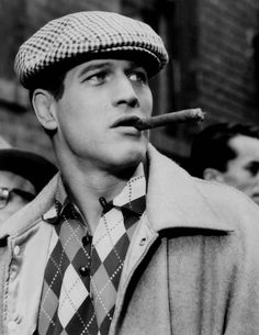 Smoking a cigar, Paul Newman is stylish in a houndstooth print newsboy cap with an argyle print shirt.